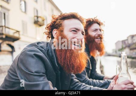 Young male hipster twins with red hair and beards on canal waterfront - Stock Photo