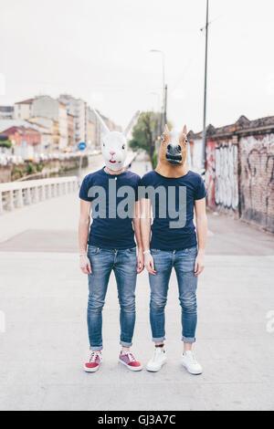 Portrait of two men wearing rabbit and horse masks on urban bridge - Stock Photo