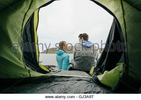 Campers relaxing in front of tent by lake, Vagar, Faroe Islands - Stock Photo