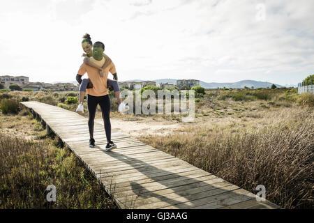 Man giving friend piggyback on wooden walkway - Stock Photo