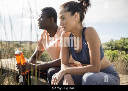 Couple wearing sports clothes sitting on wooden walkway - Stock Photo