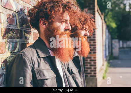 Young male hipster twins with red hair and beards leaning against brick wall - Stock Photo