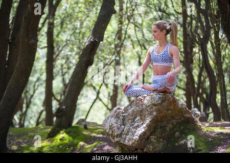 Woman on rock sitting cross legged meditating - Stock Photo