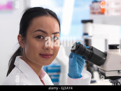 Scientist viewing a glass slide containing a sample for laboratory analysis - Stock Photo