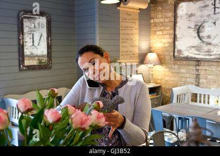 Mature female customer reading menu whilst talking on smartphone in cafe - Stock Photo