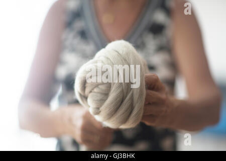 Woman holding ball of wool for felting - Stock Photo