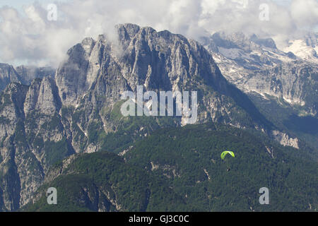 Lone paraglider paragliding in Julian Alps, Bovec, Slovakia - Stock Photo