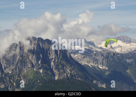 Lone paraglider paragliding in snow capped Julian Alps, Bovec, Slovakia - Stock Photo