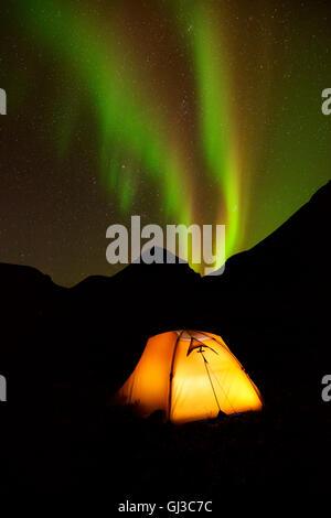 Illuminated tent and Aurora borealis at night, Khibiny mountains, Kola Peninsula, Russia - Stock Photo