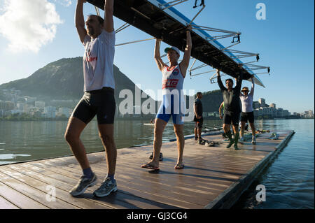 RIO DE JANEIRO - APRIL 1, 2016: Members of the Vasco da Gama rowing club carry their boat back to the clubhouse - Stock Photo
