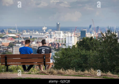LONDON - MAY 10, 2015. Two men in T-shirt with 'Dostoevsky' sign sitting on bench, admiring the view of London in - Stock Photo