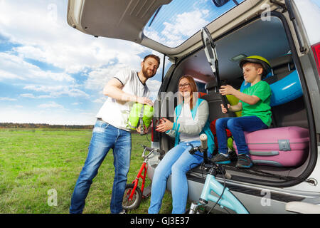 Young family loading luggage boot for the car trip - Stock Photo
