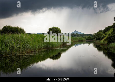 A view from Ham wall of dark clouds and heavy rain over Glastonbury tor. - Stock Photo