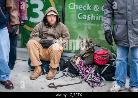 Chicago, Illinois - November 28, 2014: A Chicago homeless man and his dog sit on the sidewalk on a frigid cold day - Stock Photo