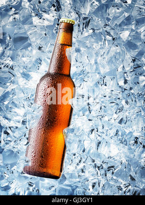 Brown bottle of beer with drops on ice cubes - Stock Photo