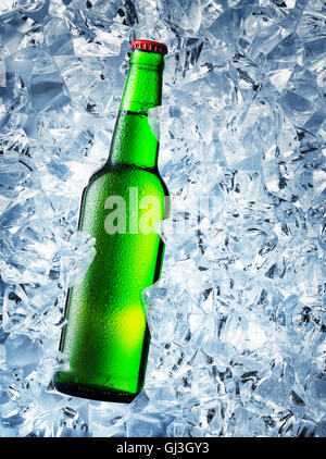Green bottle of beer with drops on ice cubes - Stock Photo