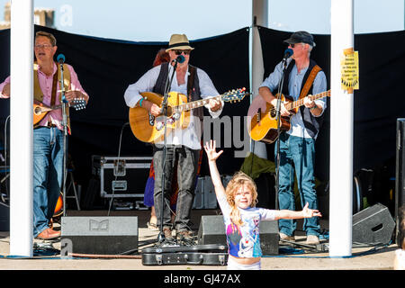 Broadstairs Folk Week Festival. Three piece senior male folk ensemble playing in the bandstand with a little child, - Stock Photo
