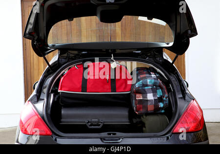 Suitcases and bags in trunk of car ready for vacation - Stock Photo