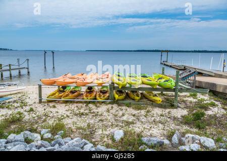 Colorful rental kayaks on rack along Perdido Bay near Perdido, Florida - Stock Photo