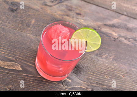 Watermelon and lime natural juice with ice cubes on rustic wood table - Stock Photo