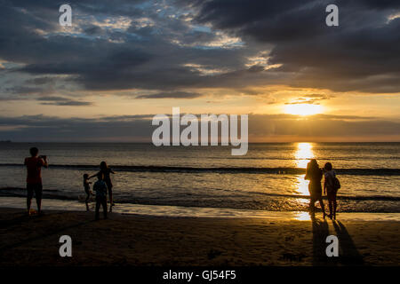 People enjoying the sunset on Tanjung Aru beach Kota Kinabau  Sabah Malaysia on the Island of  Borneo. - Stock Photo