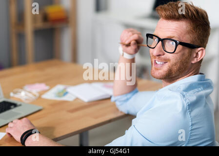 Positive man sitting at the table - Stock Photo