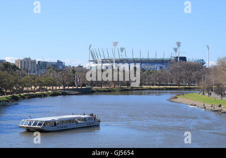 Sightseeing boat cruises in Yarra river MCG in background in Melbourne Australia. - Stock Photo
