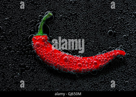 Chili pepper in a mineral water, a series of photos. Close-up carbonated water against black background - Stock Photo