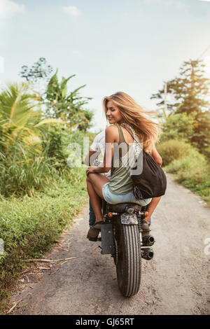Rear view shot of young couple riding motorbike on dirt road. Beautiful young woman sitting on back of her boyfriend - Stock Photo