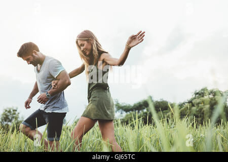 Outdoor shot of young couple walking through meadow hand in hand. Man and woman talking walk through grass field - Stock Photo
