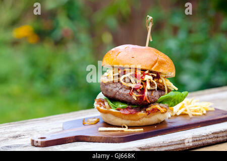 Beefburger with fried onions, bacon and string fries in brioche bun - Stock Photo