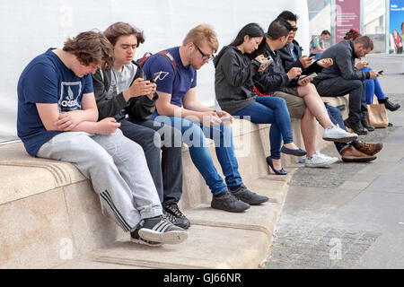 People sat down all on mobile cell phones - Stock Photo
