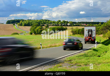 Car and truck driving on winding country road, storm clouds, motion blur, Thuringia, Germany - Stock Photo