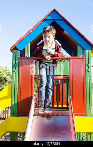 A young boy poses for a photograph at the top of a slide in a children's playground. - Stock Photo