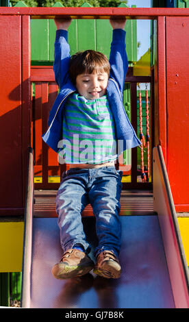 A young boy plays on a slide in a children's playground. - Stock Photo