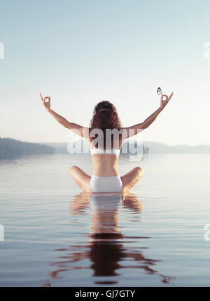 Artistic concept of a woman meditating with a butterfly on her hand. Practicing meditation on a floating platform - Stock Photo