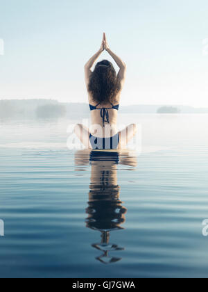 Artistic photo of a woman meditating on a platform in calm water on a misty lake in early morning during sunrise. - Stock Photo