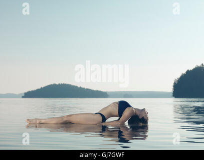 Young woman practicing yoga on a platform in water on the lake during misty sunrise in the morning. Yoga Fish posture, - Stock Photo