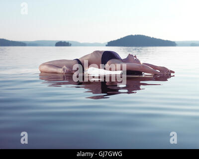 Young woman practicing sunrise yoga on a platform in calm water on the lake during misty morning. Yoga Fish posture, - Stock Photo
