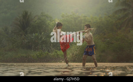 Action: Muay Thai outdoor on the river Note markings in boxer shorts, Muay Thai is a sign that the public does not - Stock Photo