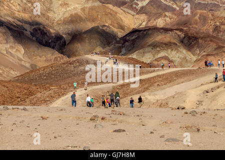 Tourists hiking on the volcanic and sedimentary hills near Artist's Palette in Death Valley National Park, California, - Stock Photo