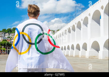 RIO DE JANEIRO - MARCH 06, 2015: Athlete draped with Olympic flag stands outdoors in the plaza at the famous Lapa - Stock Photo