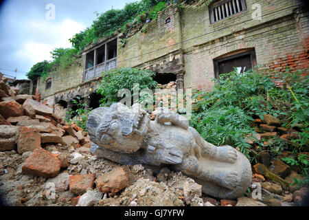Kathmandu, Nepal. 13th Aug, 2016. A Broken Stone lion sculpture thrown around the premises as Bushes and Grasses seen taller around Heritage monuments at Bungamati, Patan. Due to the delay on reconstruction of Ancient Heritage monuments, Bushes and grass becomes taller around Monuments Heritage Sites. Most of the heritage site were affected by last year's disaster Earthquake in Nepal. © Narayan Maharjan/Pacific Press/Alamy Live News