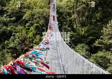 Ghasa, Nepal - November 05, 2014: Local people crossing a suspension bridge on the Annapurna Circuit - Stock Photo