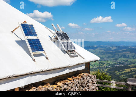 Portable solar panels on the roof of a house in the mountains. - Stock Photo