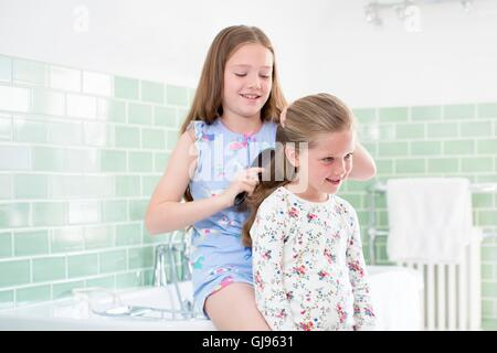 PROPERTY RELEASED. MODEL RELEASED. Big sister brushing little sister's hair in bathroom. - Stock Photo