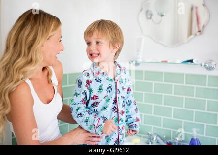 PROPERTY RELEASED. MODEL RELEASED. Mother and son in bathroom brushing teeth. - Stock Photo