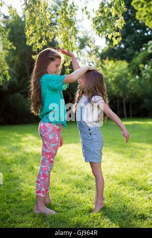 PROPERTY RELEASED. MODEL RELEASED. Two sisters measuring their height against each other. - Stock Photo