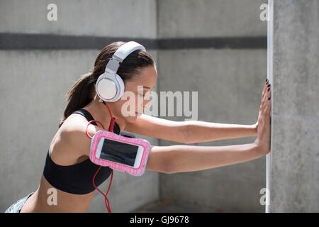 MODEL RELEASED. Young woman wearing headphones and sports band stretching against wall. - Stock Photo