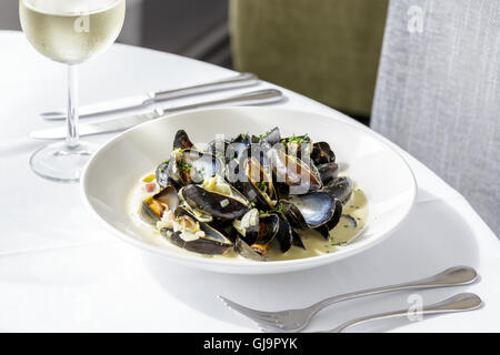 Mussels, Moules Mariniere served on white plate in restaurant - Stock Photo